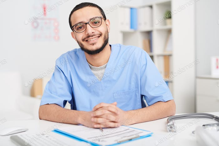 Smiling Middle-Eastern Doctor Posing at Desk