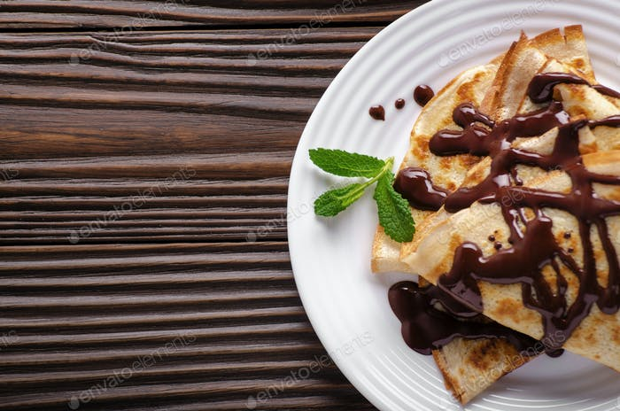 Flat lay French crepes with chocolate sauce in ceramic dish on w