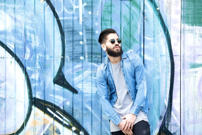 Male fashion model with  sunglasses posing by graffiti