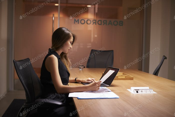 Young Asian businesswoman working alone late in an office