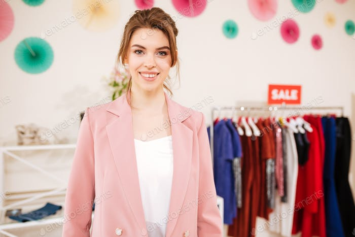 Beautiful young girl in pink jacket standing in boutique with sale clothes rack on background