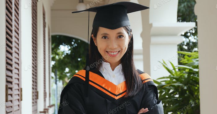 Woman wearing graduation gown in university campus