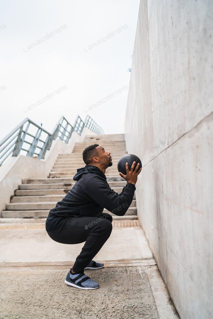 Athletischer Mann macht Wand Ball Übung.