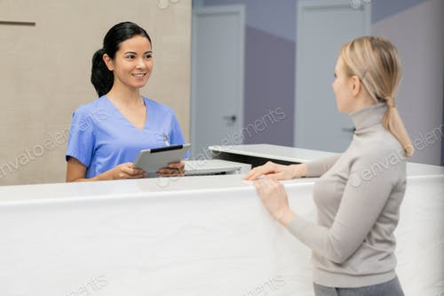 Pretty young consultant with tablet standing by reception counter