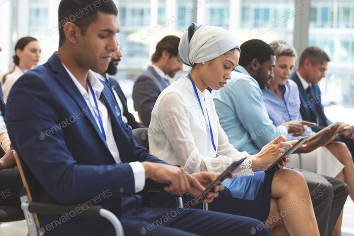 Side view of diverse business people using digital tablet during seminar in office building