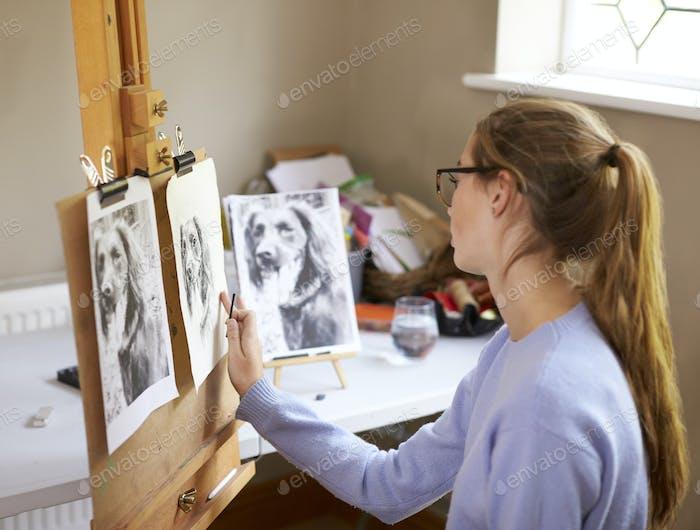 Seitenansicht des weiblichen Teenager-Künstlers sitzen an Staffelei Zeichnung Bild von Hund von Foto