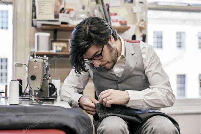 Man sewing suit by hand in family tailor business