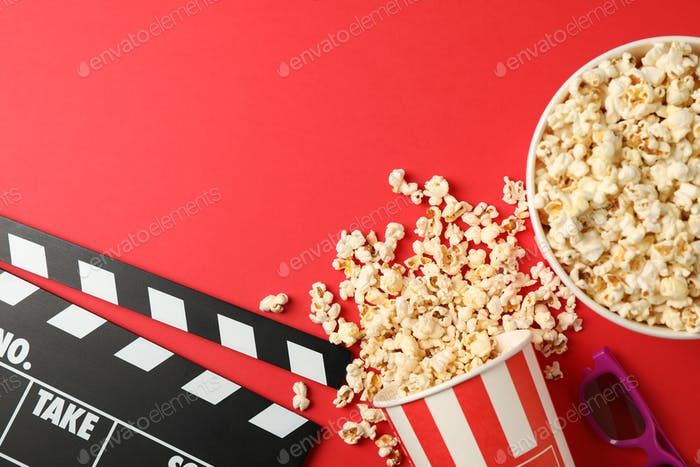 Flat lay. Buckets with popcorn, 3d glasses and clapperboard on red background