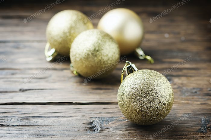 Golden christmas balls on the wooden table