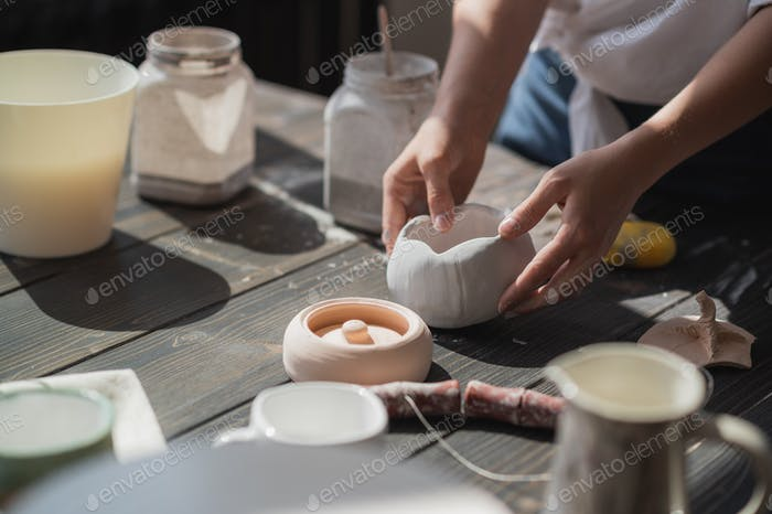 Production process of pottery. Application of glaze brush on ceramic ware