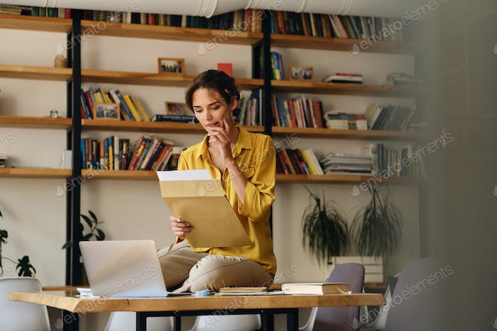 Young woman in yellow shirt sitting on desk with laptop dreamily working with papers in office