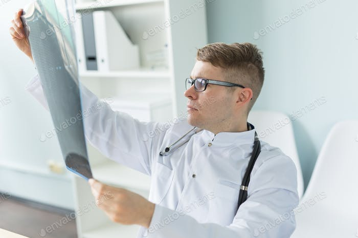 Handsome bearded doctor checking X-ray image