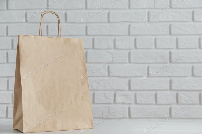 Mock-up of brown paper bag with white brick wall in background.