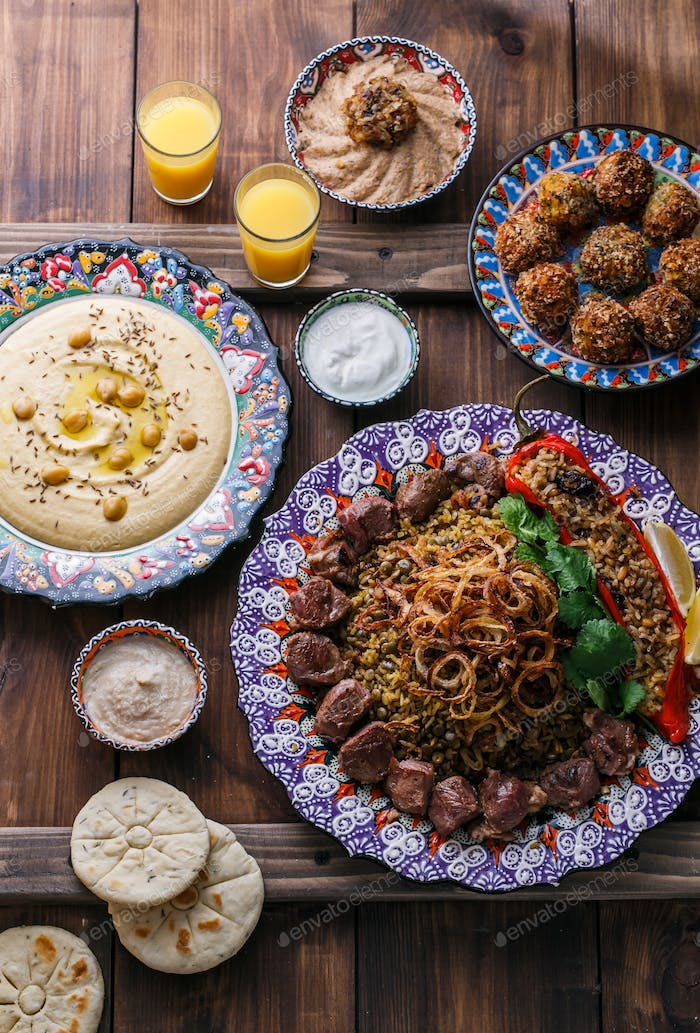 Middle eastern or arabic pilaf with hummus, falafel, eggplant dip and pitas top view