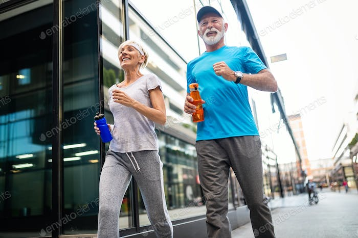 Senior woman and man running doing fitness exercises