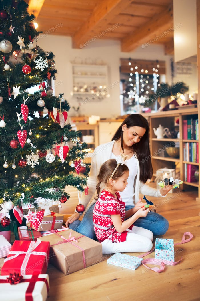 Young mother with daugter at Christmas tree at home.