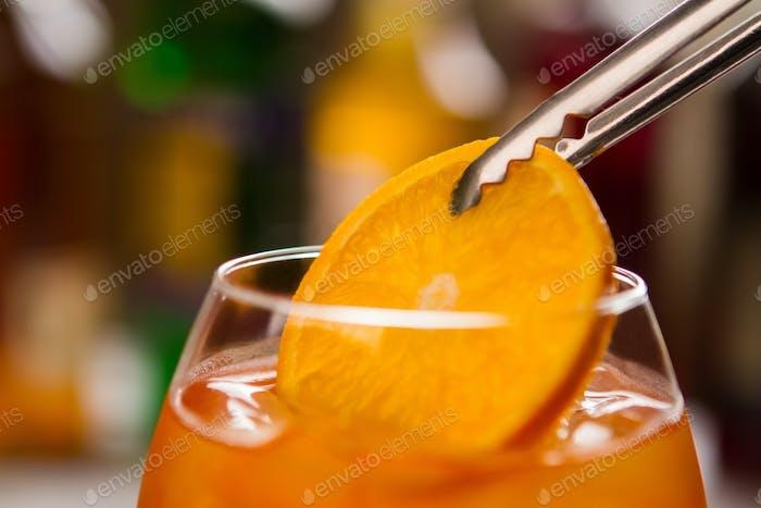 Tongs hold orange slice