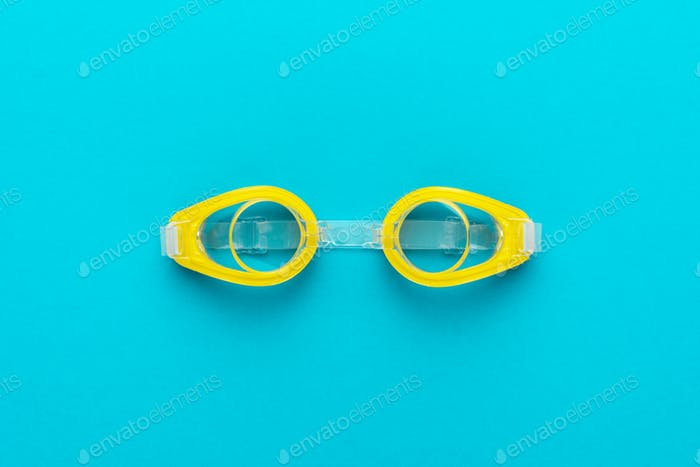 Yellow Swimming Goggles Over Blue Background With Central Composition