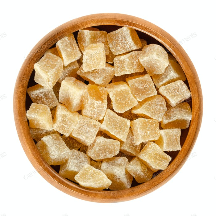 Candied ginger root cubes in wooden bowl over white