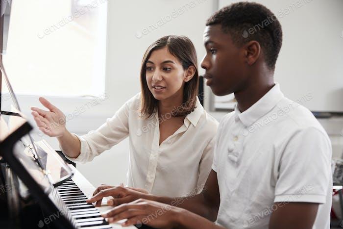 Männlich Schüler mit Lehrer spielen Klavier in Musik Lektion