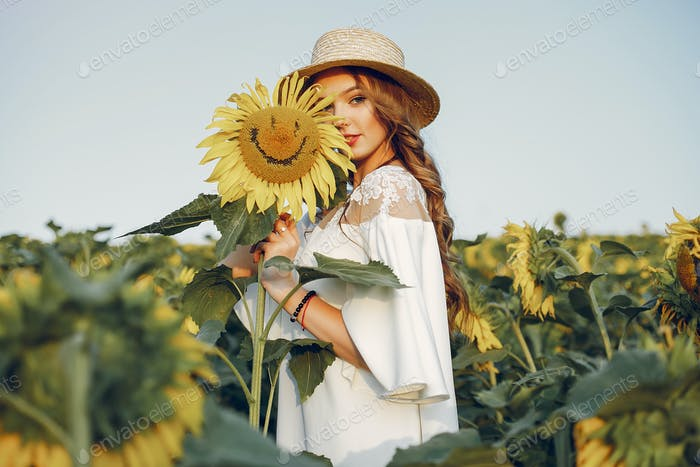 Beautiful and stylish girl in a field wirh sunflowers