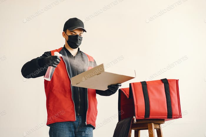 Delivery man spray sanitizing on a box