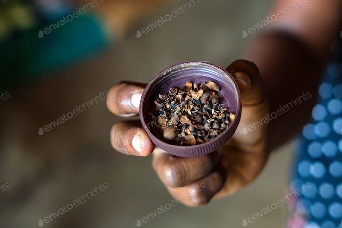 Hand holds herbal tea of Bael flowers