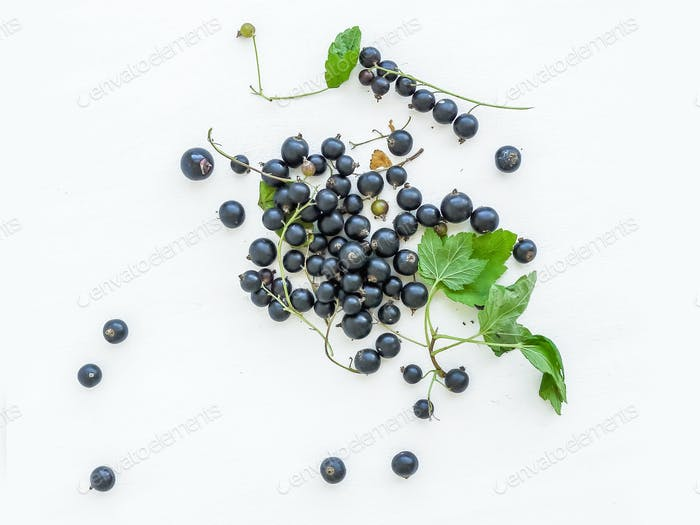 Black-currant berries and green leaves over a white wooden sufra