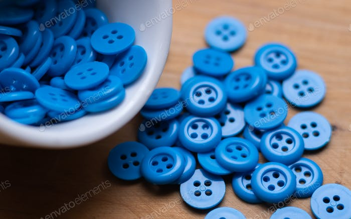 Blue button on wooden table