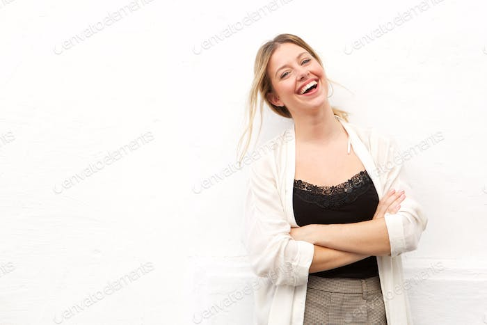 young woman laughing against white wall