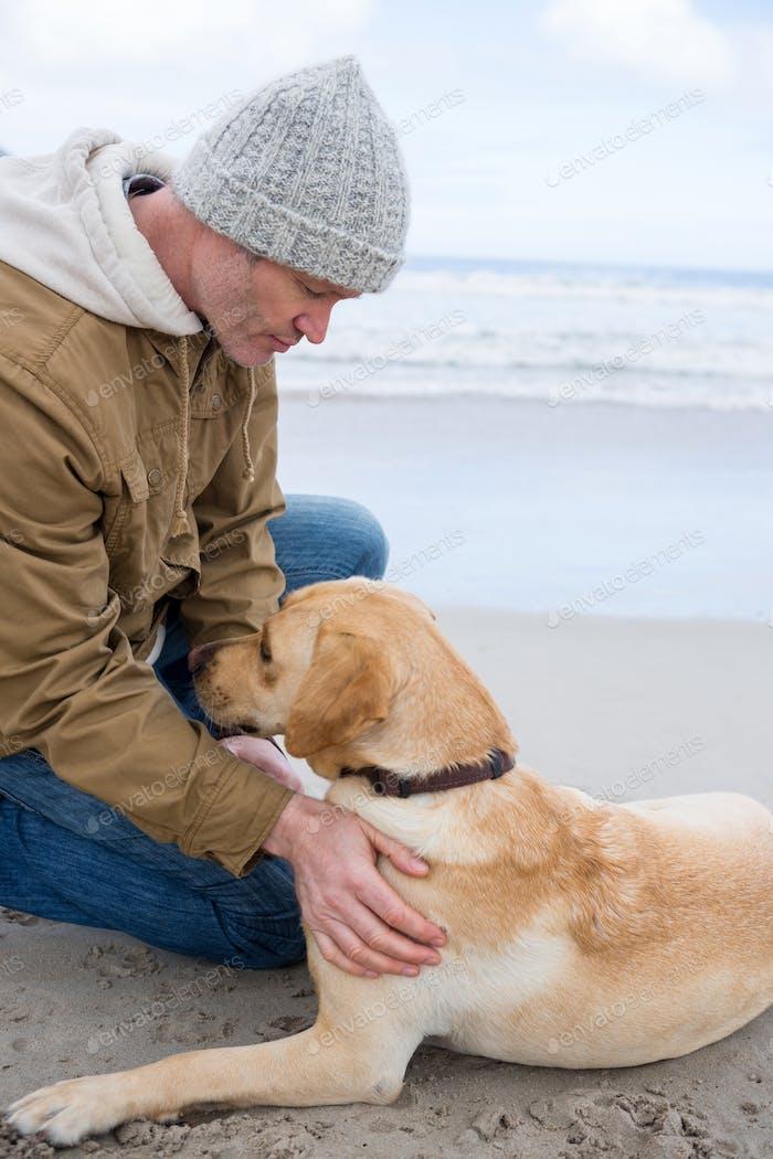 Man pampering dog while sitting