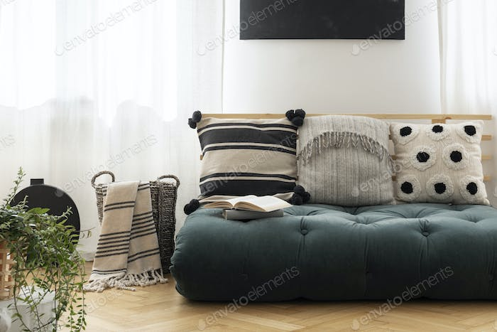 Patterned cushions on green futon in bright living room interior