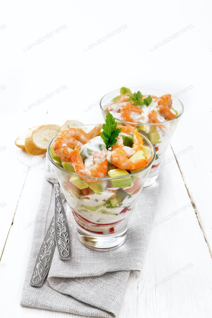 Salad with shrimp and avocado in two glasses on wooden board