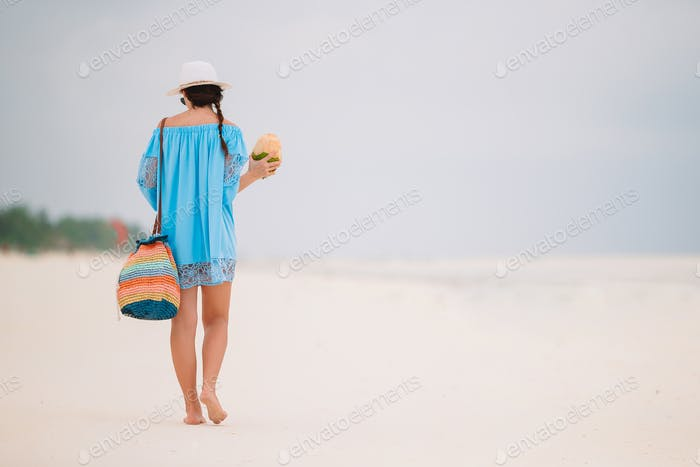 Young woman drinking coconut milk during tropical vacation