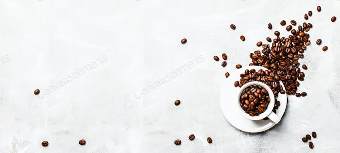 Coffee background, roasted coffee beans in a white cup, top view