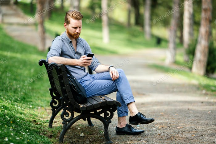 Handsome guy using phone in park