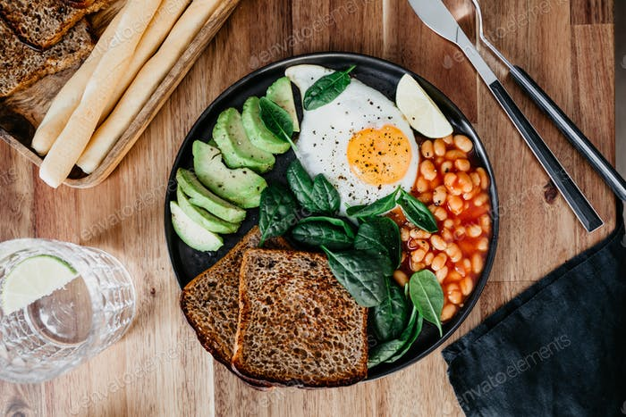 Healthy breakfast or lunch with fried egg, avocado, toasts, beans and fresh spinach
