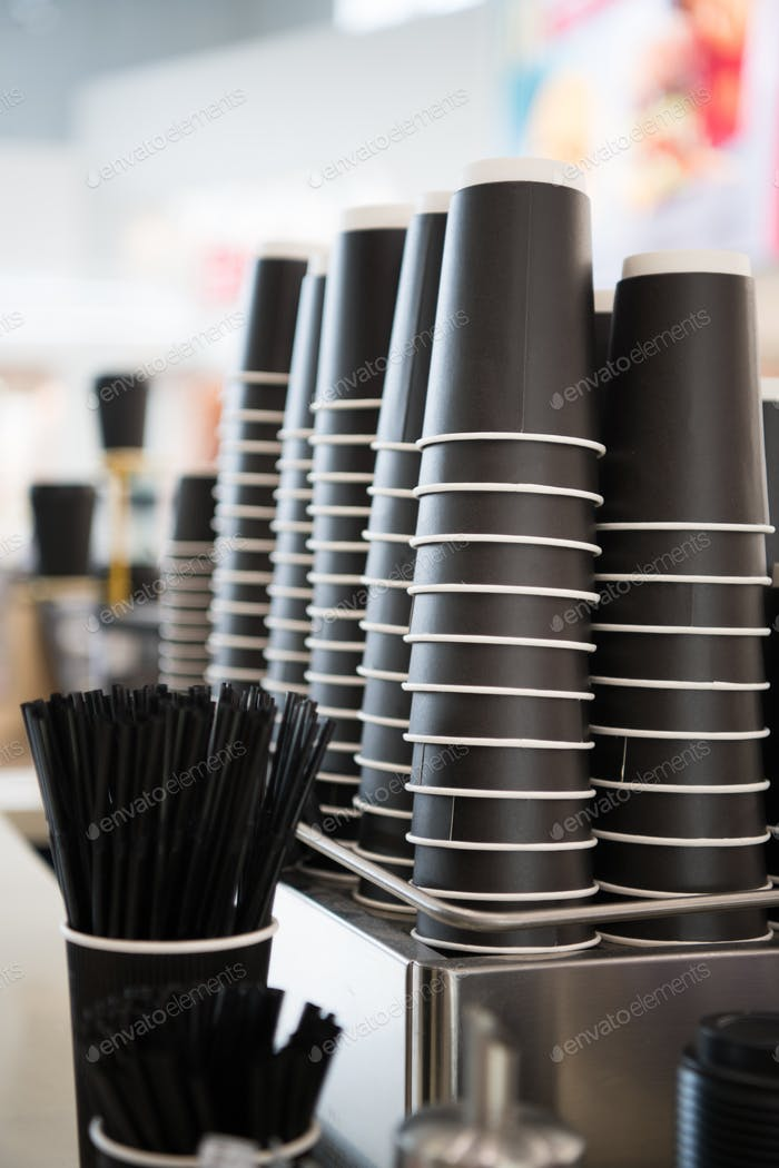 Black paper cups on a counter against the background of a blurred coffee bar at mall with takeaway