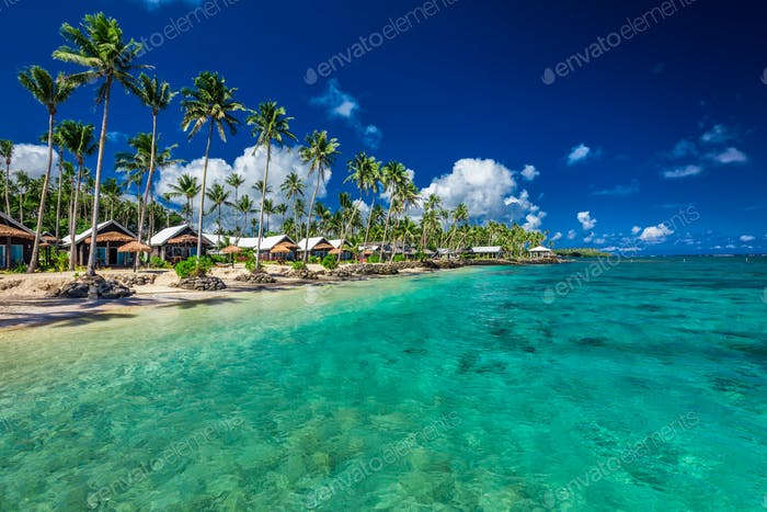 Tropical beach with with coconut palm trees and villas on Samoa