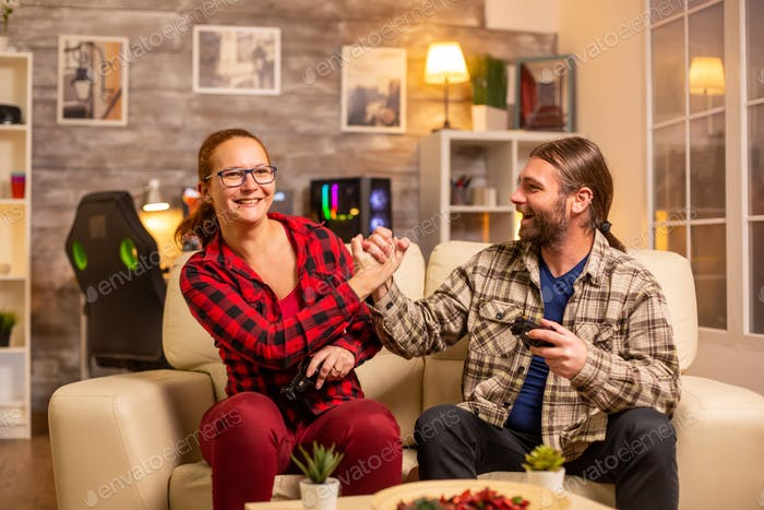 Gamers couple playing video games on the TV with wireless controllers in hands