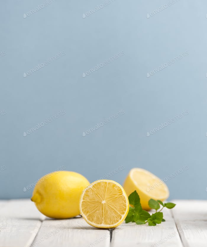 Ripe lemons and mint leaves on a white wooden table on a blue ba
