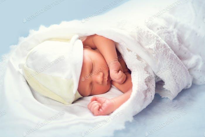 Liebenswert Neugeborenes Baby schlafen im Regal in der Kommode