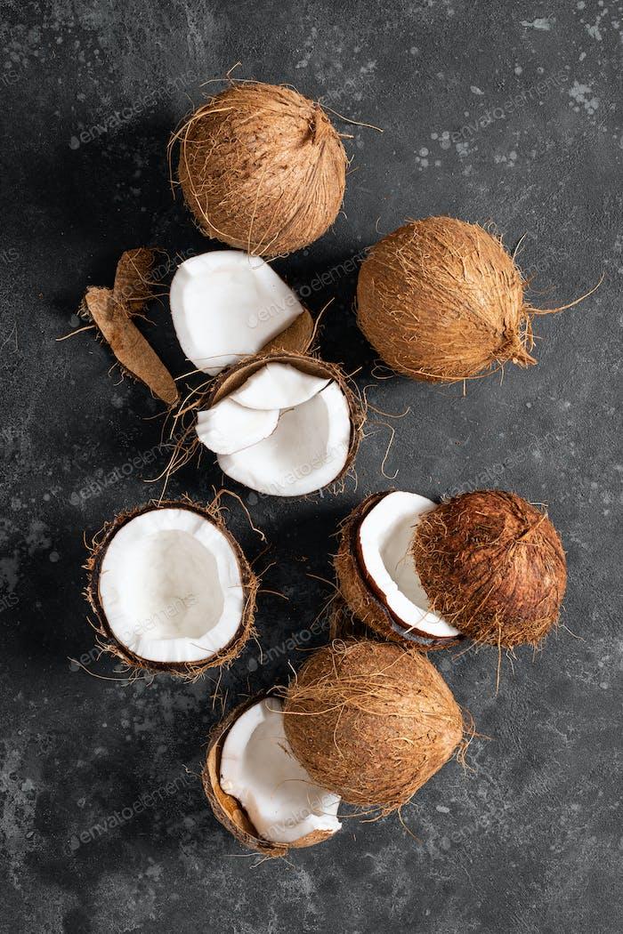 Kokosnüsse geknackt und ganz auf schwarzem Hintergrund, Draufsicht