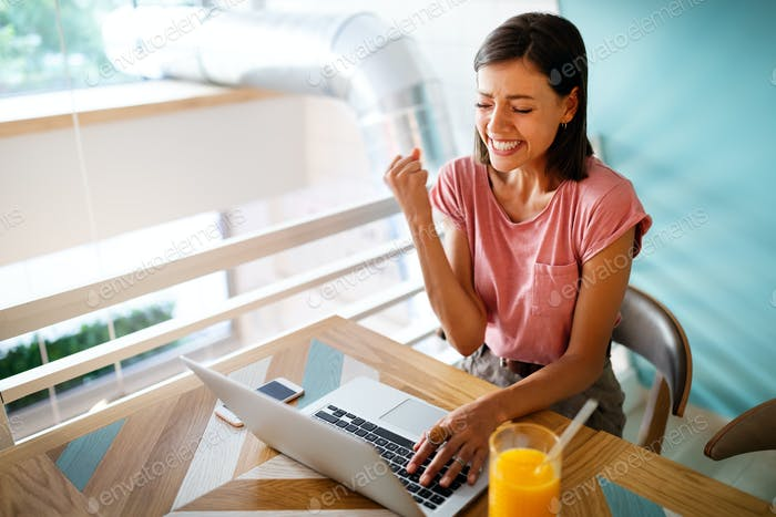 Portrait of a cheerful beautiful woman working, studying on a laptop