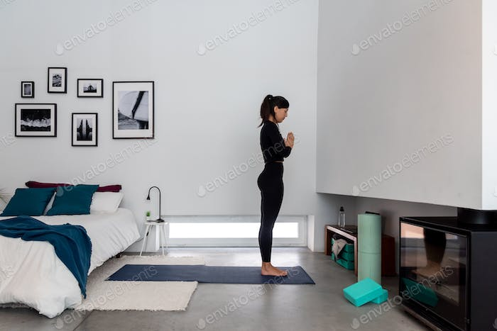 Young woman in sportswear with namaste hands and meditating during yoga practice at home