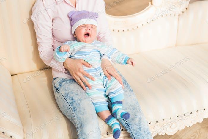 Newborn baby yawning. Wearing cute blue sweater