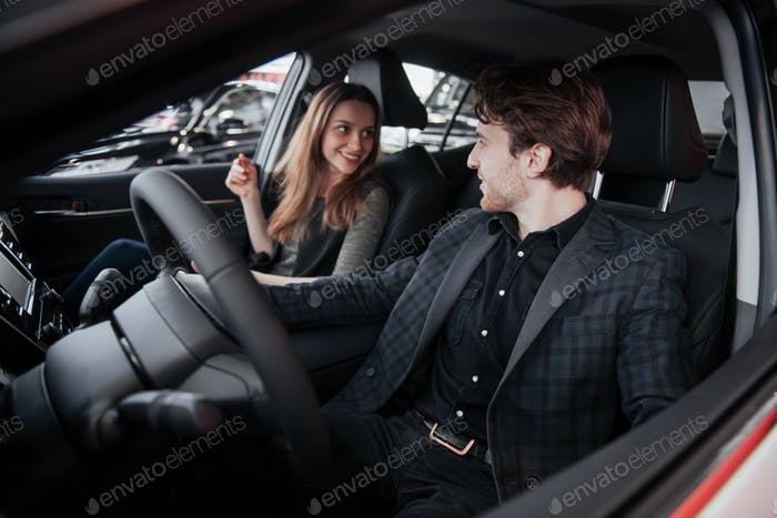 Check put the stereo system! Handsome mature man smiling at his wife turning on music while sitting