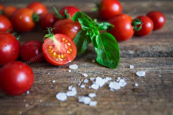 Frische Traubentomaten mit Basilikum und grobem Salz zur Verwendung als Kochzutaten