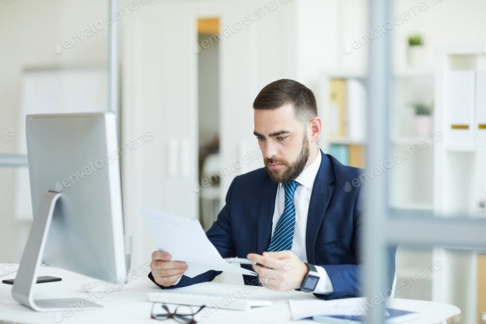 Busy manager examining contract