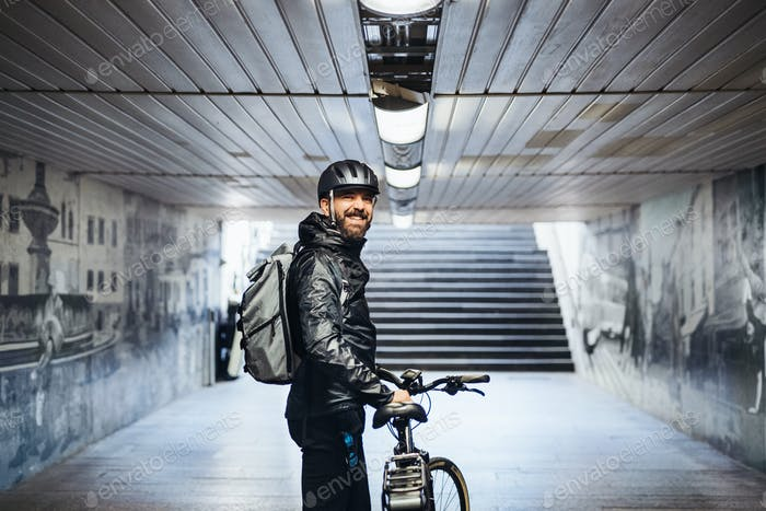 Male bicycle courier standing in subway when delivering packages in city.